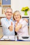 Couples supérieurs heureux tenant des pouces  Photographie stock