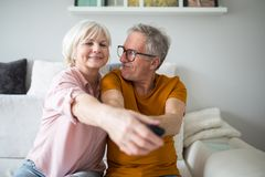 Couples supérieurs heureux tenant l'extérieur de TV ensemble Photo libre de droits