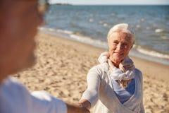 Couples supérieurs heureux tenant la plage d'été de mains Photo stock