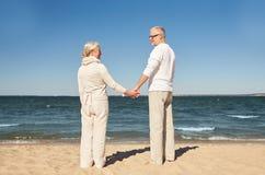 Couples supérieurs heureux tenant la plage d'été de mains Photo libre de droits