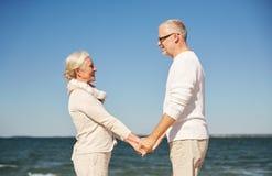 Couples supérieurs heureux tenant la plage d'été de mains Images stock