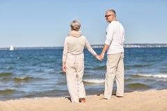 Couples supérieurs heureux tenant la plage d'été de mains Images libres de droits