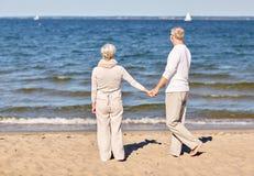 Couples supérieurs heureux tenant la plage d'été de mains Image libre de droits