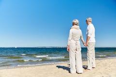 Couples supérieurs heureux tenant la plage d'été de mains Photos libres de droits