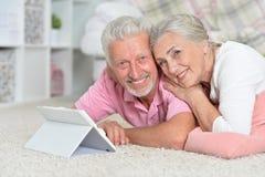 Couples supérieurs heureux utilisant le comprimé Photographie stock libre de droits