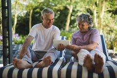 Couples supérieurs heureux utilisant le comprimé numérique sur des chaises longues Images libres de droits