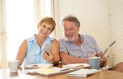 Couples supérieurs heureux utilisant le téléphone et le comprimé intelligents tout en ayant le Br photographie stock libre de droits