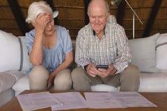 Couples supérieurs inquiétés discutant au-dessus des factures médicales image stock