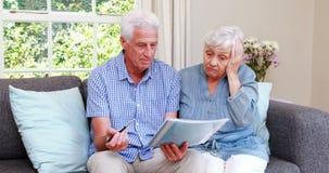 Couples supérieurs inquiétés regardant le document banque de vidéos