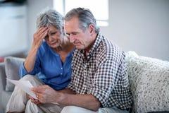 Couples supérieurs inquiétés vérifiant les factures image stock