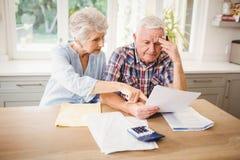 Couples supérieurs inquiétés vérifiant leurs factures image libre de droits