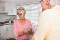 Couples supérieurs jouant des cartes au compteur Photo stock