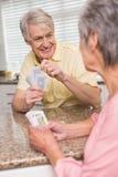 Couples supérieurs jouant des cartes au compteur Image stock