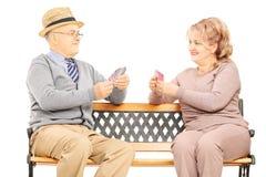 Couples supérieurs jouant des cartes posées sur le banc en bois Image stock