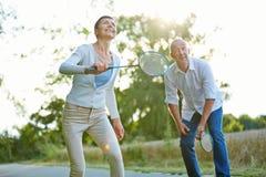 Couples supérieurs jouant le badminton Images stock