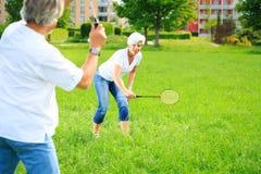 Couples supérieurs jouant le badminton Photographie stock libre de droits