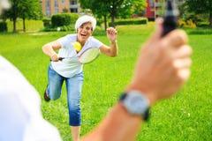 Couples supérieurs jouant le badminton Image stock
