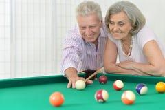 Couples supérieurs jouant le billard Image stock