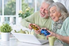 couples supérieurs jouant le jeu d'ordinateur avec l'ordinateur portable tout en buvant Image libre de droits