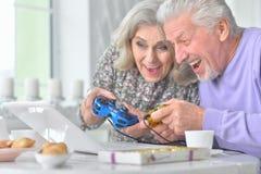 Couples supérieurs jouant le jeu d'ordinateur avec l'ordinateur portable tout en buvant t Image stock