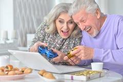 Couples supérieurs jouant le jeu d'ordinateur avec l'ordinateur portable tout en buvant t Photo libre de droits