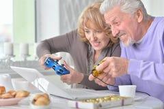 Couples supérieurs jouant le jeu d'ordinateur avec l'ordinateur portable tout en buvant t Photographie stock