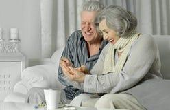 Couples supérieurs malades prenant des pilules Photographie stock libre de droits