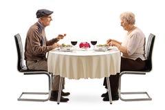 Couples supérieurs mangeant d'une salade à une table de restaurant images stock