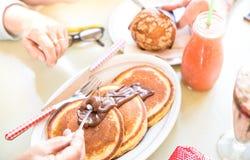 Couples supérieurs mangeant la crêpe avec du chocolat au café Images stock