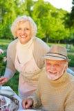 Couples supérieurs mangeant le gâteau dans le jardin Images stock