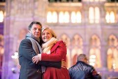 Couples supérieurs marchant dans la ville de nuit Hiver, bâtiment historique Photo stock