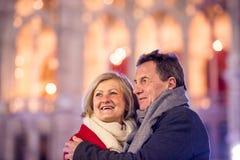 Couples supérieurs marchant dans la ville de nuit Hiver, bâtiment historique Images stock