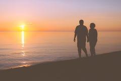 Couples supérieurs marchant le long de la plage photographie stock