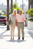 Couples supérieurs marchant le long de la rue ensemble Photo stock
