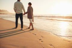 Couples supérieurs marchant le long du bord de mer Photographie stock libre de droits