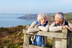 Couples supérieurs marchant le long du chemin côtier Images stock