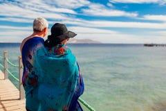 Couples supérieurs marchant sur la jetée par la Mer Rouge couverte de pareo Les gens appréciant des vacances Jour du `s de Valent photos stock