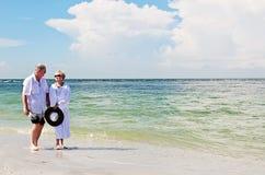 Couples supérieurs marchant sur la plage Photographie stock libre de droits