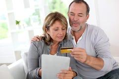 Couples supérieurs modernes à la maison faisant des emplettes avec le comprimé Photographie stock libre de droits
