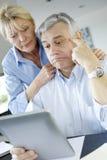 Couples supérieurs modernes rendant la déclaration d'impôts en ligne Images libres de droits