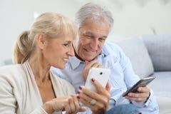Couples supérieurs modernes utilisant des smartphones Image stock