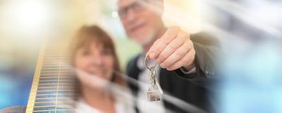 Couples supérieurs montrant des clés de maison, effet de la lumière ; exposur multiple image stock
