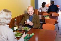 Couples supérieurs occupés avec des téléphones la date en café Photos libres de droits