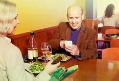 Couples supérieurs occupés avec des téléphones la date en café Images libres de droits