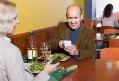 Couples supérieurs occupés avec des téléphones la date en café Photo libre de droits
