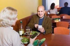Couples supérieurs occupés avec des téléphones la date en café Photo stock