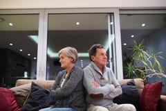 Couples supérieurs offensés se reposant sur un divan avec des bras croisés Photo libre de droits