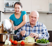 Couples supérieurs ordinaires faisant cuire avec des légumes Photos stock