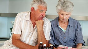 Couples supérieurs organisant leur médecine pour la semaine banque de vidéos
