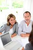 Couples supérieurs parlant à l'agent immobilier Images stock
